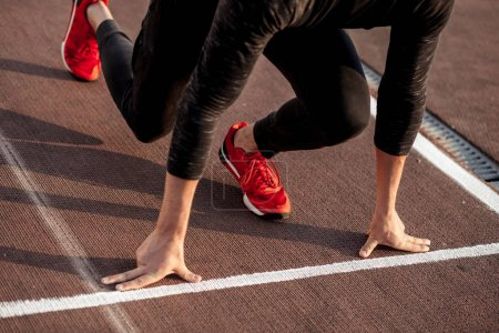 Photo for Young man wearing black clothes and red shoes in starting position for running on sports track in stadium - Royalty Free Image