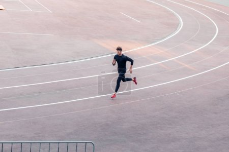 Top view Athlete running on running track. Runner sprinting on red running track in stadium