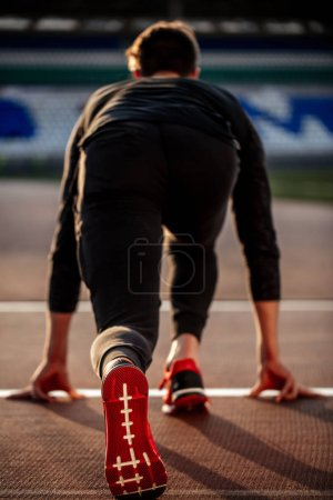 man feet in starting position for running on race track in stadium