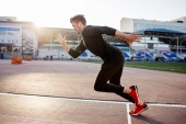 athlete in black clothes starting sprint on running track