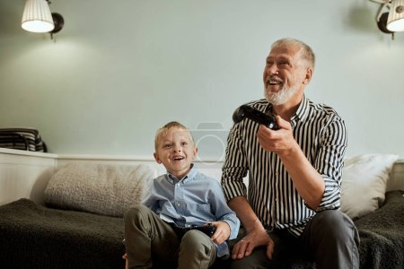 Photo for Cute little boy with grandfather sitting on sofa and playing video game with game pad - Royalty Free Image