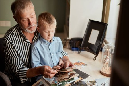 Foto de Abuelo y nieto en el sofá en casa. El abuelo y los niños viendo viejas fotos en álbum - Imagen libre de derechos