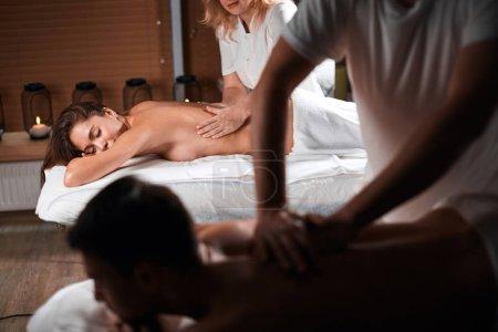 Photo pour L'heureux couple détendue se traitement de soins corporels ayant paisible calme expression en position couchée sur les lits de massage dans station thermale. - image libre de droit