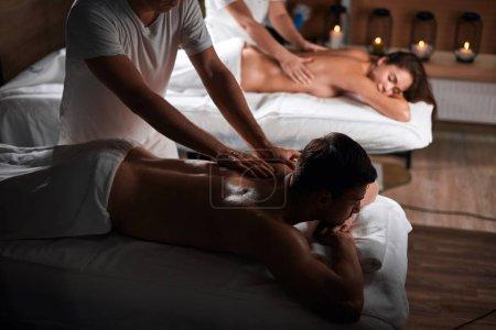 Photo pour Jeune couple reçoit un massage du dos dans un centre de Spa. Massage Massage homme beau caucasien de thérapeute. Concept santé et beauté, resort et relaxation. - image libre de droit