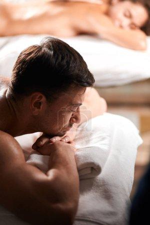 Photo pour Couple caucasien touristique en mettant l'accent sur l'homme, recevant l'huile massage du dos dans un spa centre étant heureux et satisfait avec service hôtelier-spa, rafraîchissant après le long voyage. Concept de soins de santé et bien-être - image libre de droit