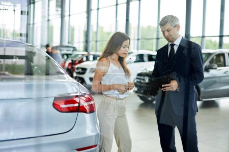 Young female customer asking mature sales manager to help in car dealership.