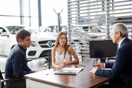 Mature sales manager signing contract with clients at car dealership office