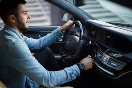 Photo for Attractive driver is turning on the vehicle. side view photo. - Royalty Free Image