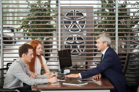 Photo pour Agent de ventes au comptoir table racontant les caractéristiques de la voiture à un couple gai de clients au bureau de concessionnaire de voiture - image libre de droit