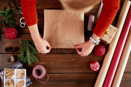 Woman s hands wrapping Christmas gift on dark wooden background.