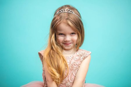 Photo for Portrait of happy shying little girl in pink princess dress isolated on blue background - Royalty Free Image