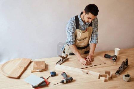 Photo pour Entouré de concentré ébéniste caucasien, rédaction de notes sur papier pour l'artisanat vierge couchée sur un bureau en bois à l'atelier, outils de menuiserie et les détails en bois, concept d'atelier de meubles - image libre de droit