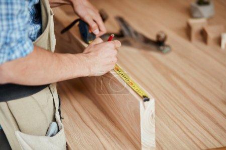Photo pour Accueil concept rénovation - caucasien masculin ébéniste dans le tablier mesure de planche de bois avec une règle souple, gros plan - image libre de droit