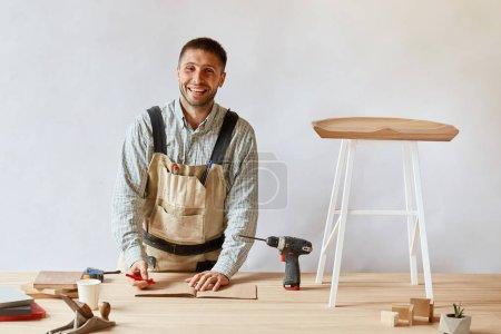 Photo pour Menuisier souriant à la caméra tandis que vous travaillez couché dessin technique sur au studio, entouré d'outils de menuiserie et de planches de bois, de fabrication de meubles ou de processus de rénovation de maison - image libre de droit