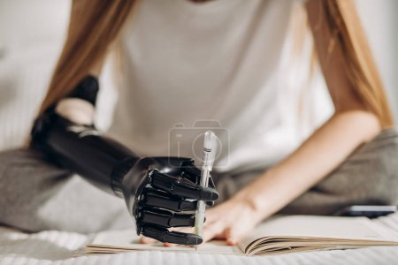 Photo for Ability of controlling artificial arm. writer with a prosthetic arm creatinf a novel, art, willpower. - Royalty Free Image