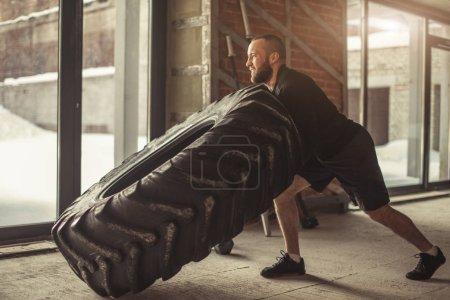Photo pour Athlète fort retournant un pneu énorme dans le studio CrossFit avec des murs de briques minimalistes à l'intérieur. Il s'agit d'un exercice qui simule simultanément un soulèvement brutal des genoux et une poussée vers le haut . - image libre de droit