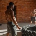Caucasian athlete exercising with sledge hammer Hi...