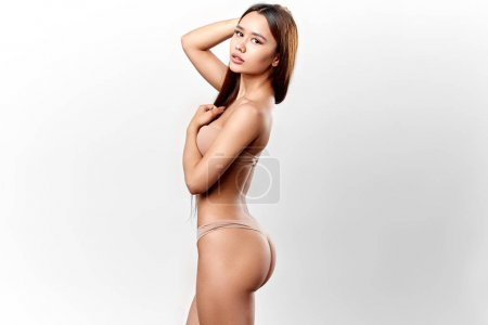 Photo for Slim model with a hand on her head showing her perfect belly and butt. isolated white background, studio shot . lifestyle. - Royalty Free Image