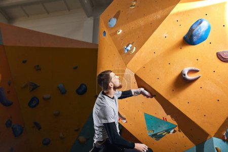 Photo for Young motivated rock-climber trains hard in climbing gym club, gets ready to bouldering competition among people with physical disabilities. Motivation and sport concept. - Royalty Free Image