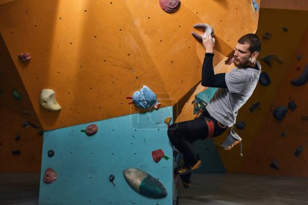 Photo for Handsome athletic boulderer with beard training hard at indoor climbing settings after warming up exercises, going to pass exam on instructor certificate. Active sport concept. - Royalty Free Image