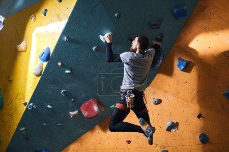 Photo pour Homme physiquement handicapé actif bien formé pratiquant un nouveau passe-temps extrême dans le bloc de gymnastique, faisant des progrès, appréciant l'escalade sur une paroi de roche artificielle. Vue arrière, plan complet . - image libre de droit