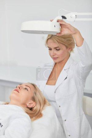 Foto de Chica de pelo rubio quiere la cara de limpieza, ser examinado por el talentoso terapeuta bajo la lámpara. Cuidado de la piel, cosmetología, medicina estética concept.close up foto - Imagen libre de derechos