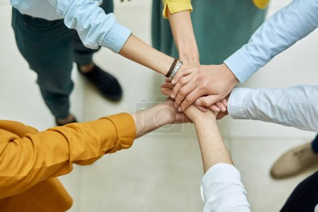 Photo for Friends keep hands together in sign of friendship and unity, shot from above, background of light coloured floor, people peace concept - Royalty Free Image