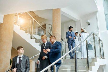 Photo pour Caucasian men go speaking, having conversation after conference with sheikhs. Business center background - image libre de droit