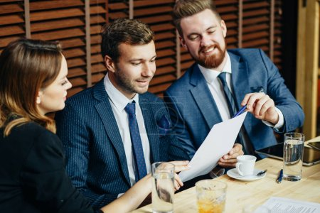 Photo pour Closeup of joyful business men in white shirts and blue jackets together with a girl in black suit sitting at table and reading terms of contract - image libre de droit