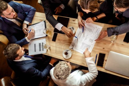 Photo pour Top view of business people sitting around wooden table, putting pens on paper document, conversation with animation thinking over strategic decision. Concept d'entreprise - image libre de droit