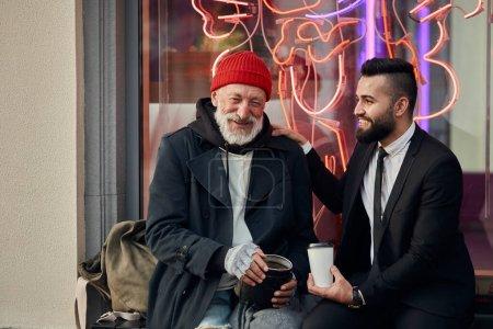 Photo pour Homme d'affaires joyeux et miséricordieux assis à côté d'un clochard souriant en chapeau rouge et manteau, homme riche en smoking noir - image libre de droit