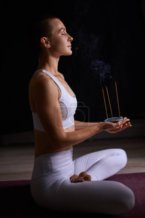 Photo pour Attractive caucasian woman in white sportclothes sit on mat and meditate, breathes. Smoke from candles, aromatic sticks in hands. Black background - image libre de droit