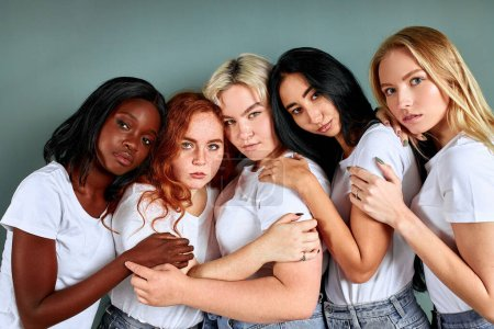 Photo for Portrait of five attractive women in jeans standing together isolated over grey background - Royalty Free Image