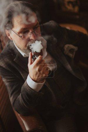 Photo pour Mari anxieux dans une veste de tweed assis à la maison, gonflant nerveusement sa pipe, s'inquiétant pour sa femme qui n'est pas encore venue en cette fin de soirée. - image libre de droit