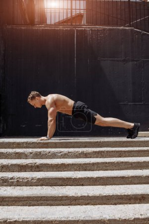 Photo for Sports and healthy lifestyle. Young bare chested man doing push-ups on the urban park staircase - Royalty Free Image
