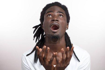 Photo pour Jeune homme levant les yeux et ne disant pas Dieu ou pourquoi avec les mains levées - image libre de droit