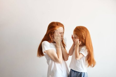 Photo for Of red haired mother and daughter hugging over white background with copyspace indoor - Mum enjoying time with her kid - Family lifestyle, people relationships and love concept - Red-haired Beauty - Royalty Free Image