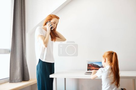 Photo for Happy redheaded mother and daughter spending time together , The little girl doing homework using laptop computer at home while her mother talking on phone at white and well-lit living room - Royalty Free Image