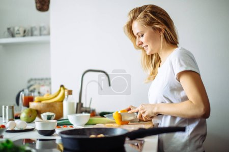 Young female chef cooking in kitchen