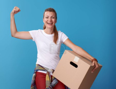 smiling active woman in white shirt holding a cardboard box on blue background