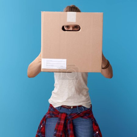 active hipster in white shirt looking through a cardboard box isolated on blue