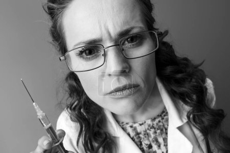 pediatrician doctor in white medical robe with syringe isolated on