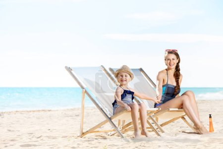 happy modern mother and daughter in swimsuit on seashore sitting on beach chairs