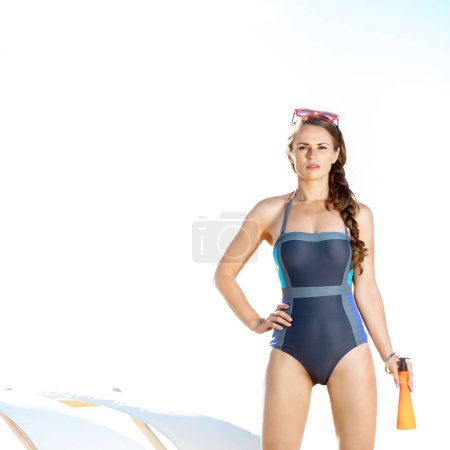 young woman in swimsuit on the seacoast with suntan lotion