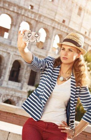 mujer de viajero moderno en un sombrero de paja cerca de tomar Coliseo selfie con teléfono móvil