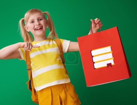 Photo for Smiling school girl with backpack pointing at shopping bag with stationery on green background - Royalty Free Image