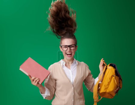 Photo for Happy modern student woman with book and backpack jumping on green background - Royalty Free Image