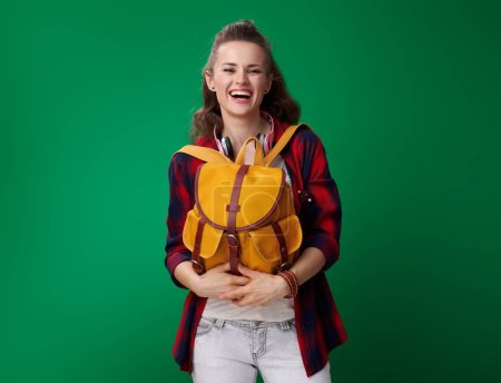 smiling young student woman in red shirt with headphones on neck holding backpack in front of belly and looking at camera on green background
