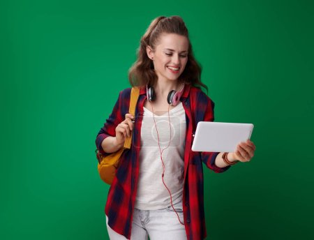 smiling young student woman in red shirt with backpack and headphones using tablet PC on green background