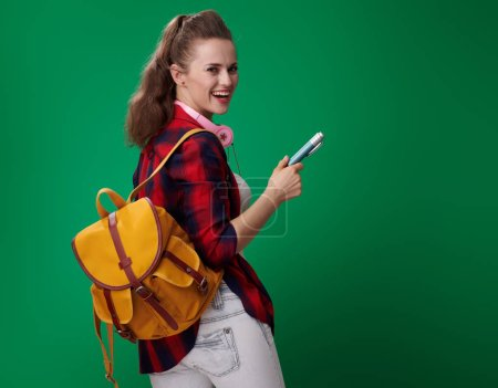 back view of happy modern student woman in red shirt with backpack and headphones holding big pen on green background